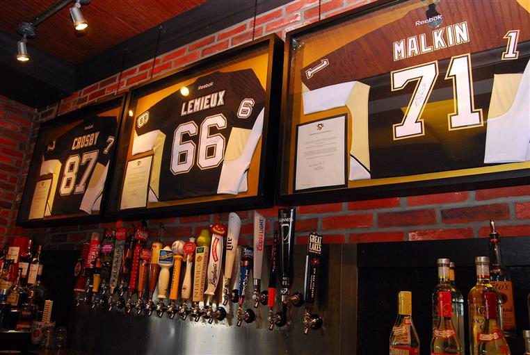 Sports jerseys hung on the wall above a bar.