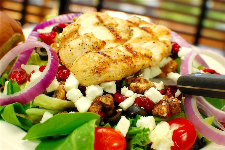 Chicken Salad with greens, grilled chicken, red onion, and tomatoes.