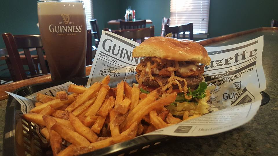 A burger served with French fries by a glass of Guiness beer
