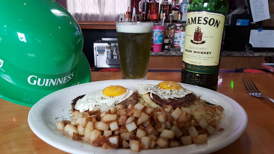 A dish of two fried eggs over two beefs served with a side of fried potatoes, in fronτ of a Glass with Guiness beer and a bottle of Jameson whiskey