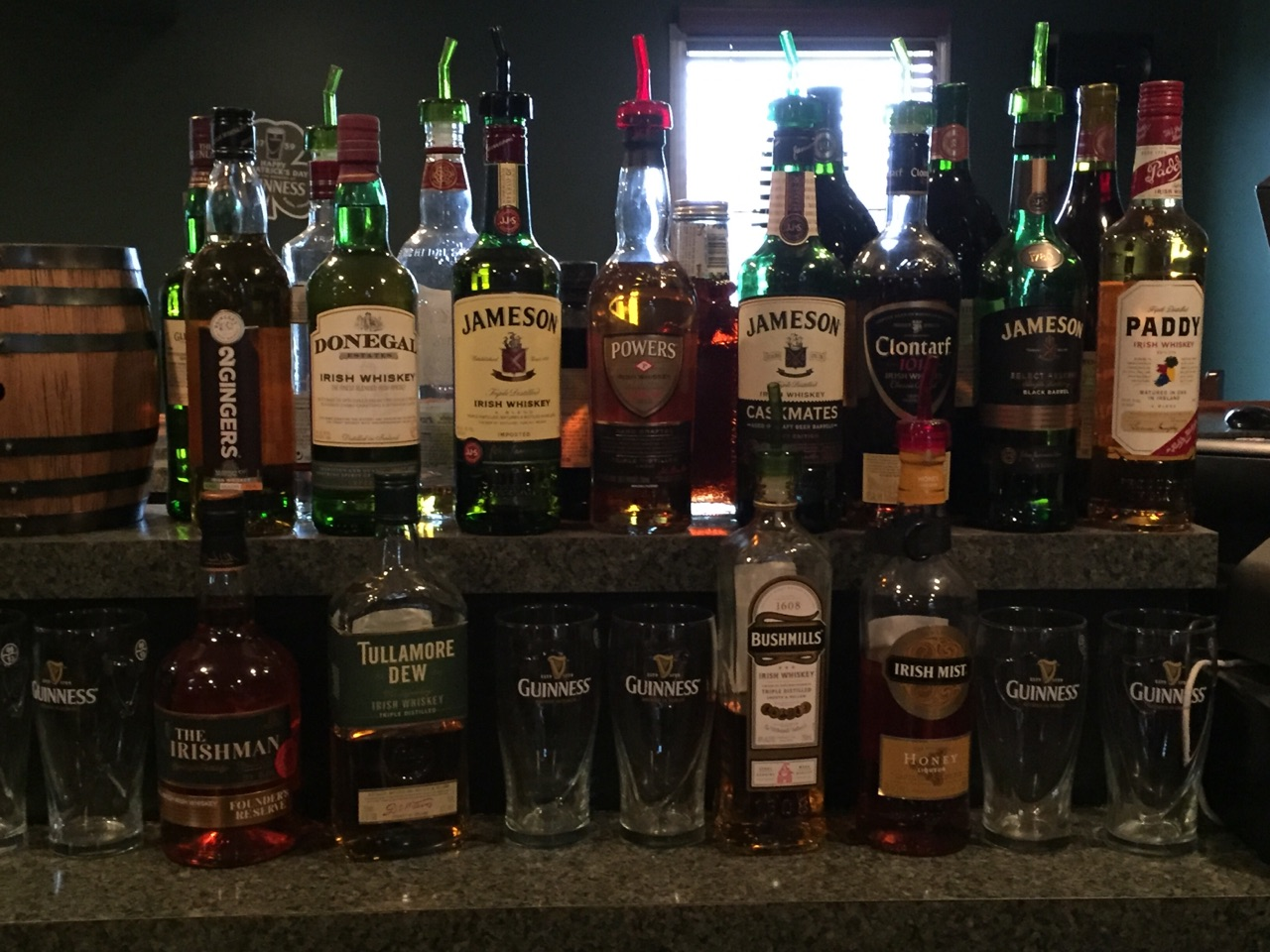 Bottles of several types of whisky, and beer Glasses, on the bar.