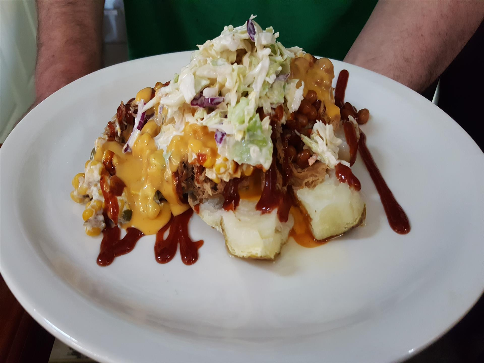 A dish of baked potato with pulled pork, baked beans, kickin' corn, slaw, BBQ sauce and cheddar sauce