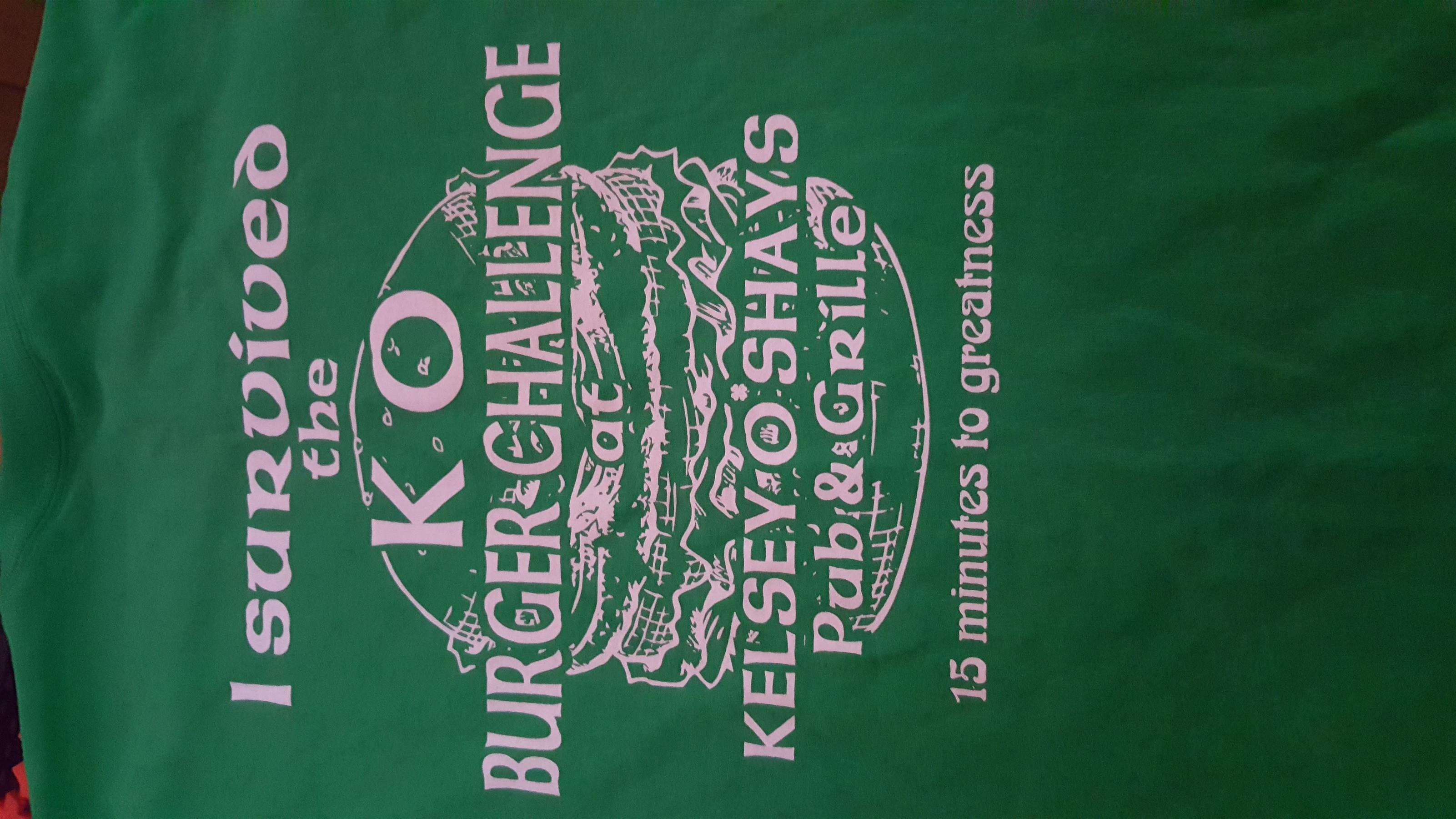 A green t-shirt with the KO Burger challenge written in white