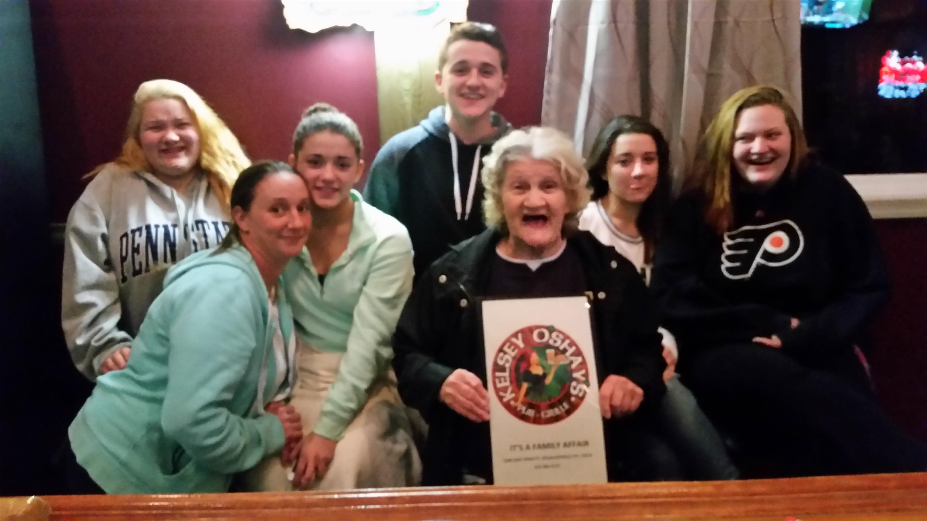 Smiling young people beside a happy winner of the Pub's Challenge