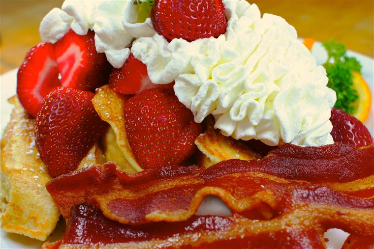 Pancakes topped with strawberries and whipped cream with a side of bacon