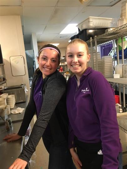 Two smiling young women in the restaurant's kitcher posing for a photo
