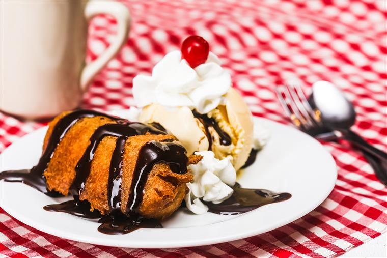 Fried dessert with chocolate syrup drizzled on top with a scoop of vanilla ice cream with a cherry and whipped cream on the side
