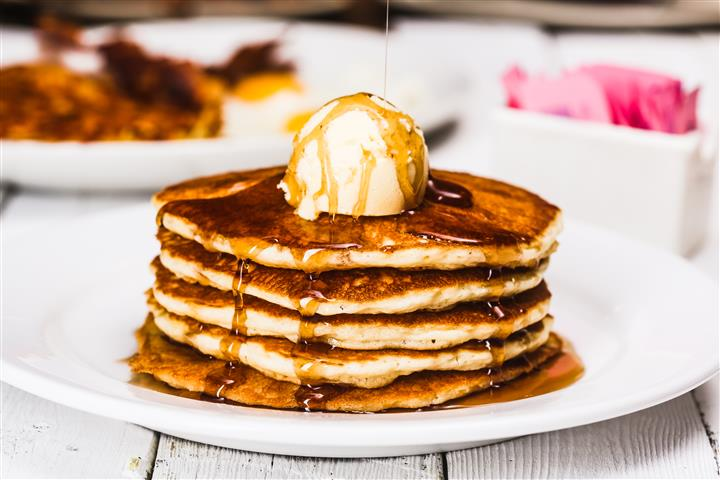 Stacked pancakes with syrup and a dallop of butter on top