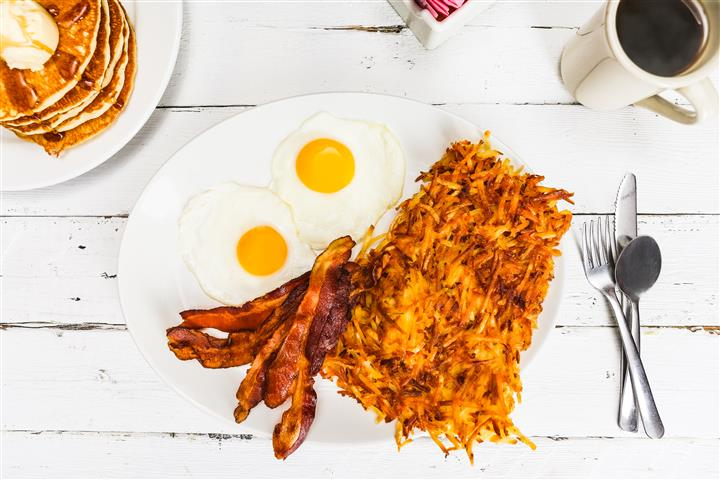 Hash browns with a side of bacon and two sunny side up eggs on a plate