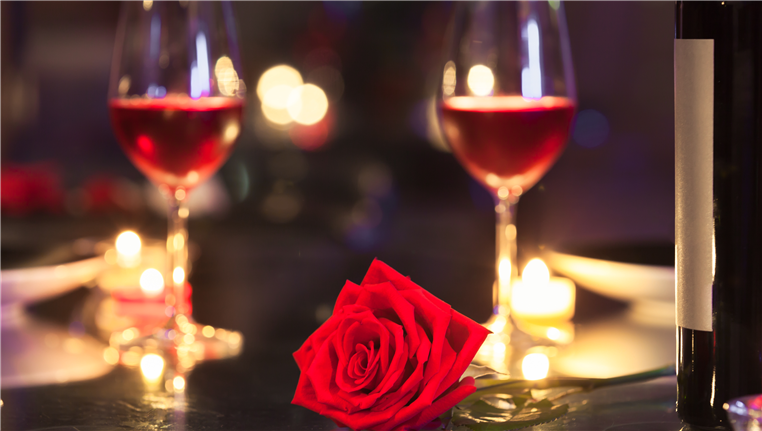 2 wine glasses and a rose on table
