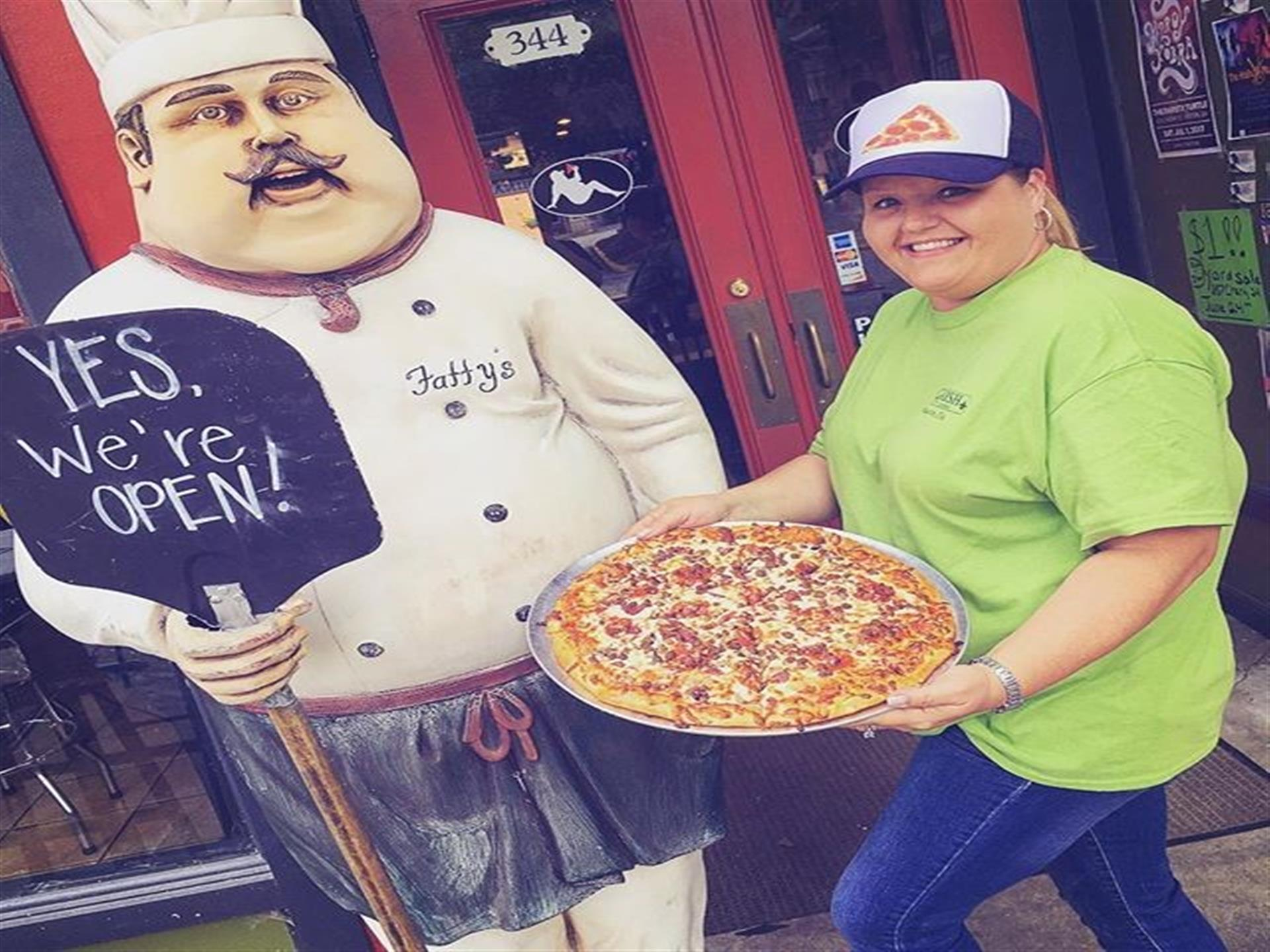 female outside holding a pizza