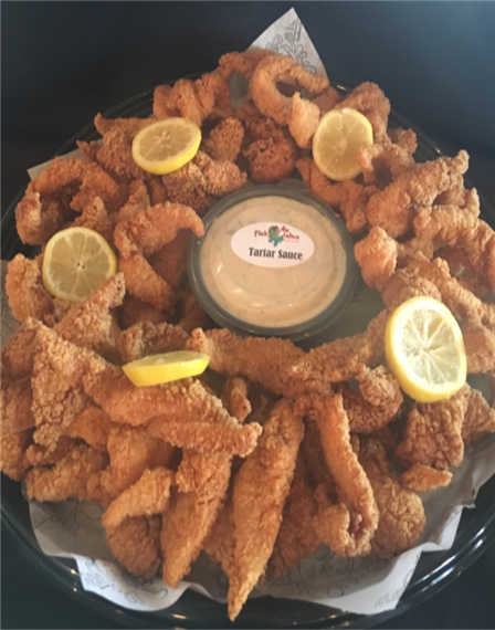 Fried seafood dish served with tartar sauce and lemon slices