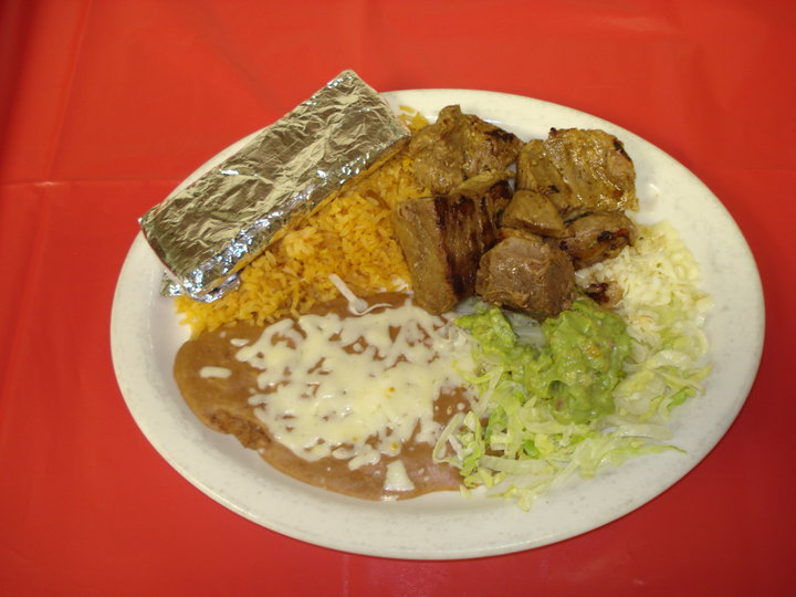 Mexican dish served with guacamole and shredded lettuce