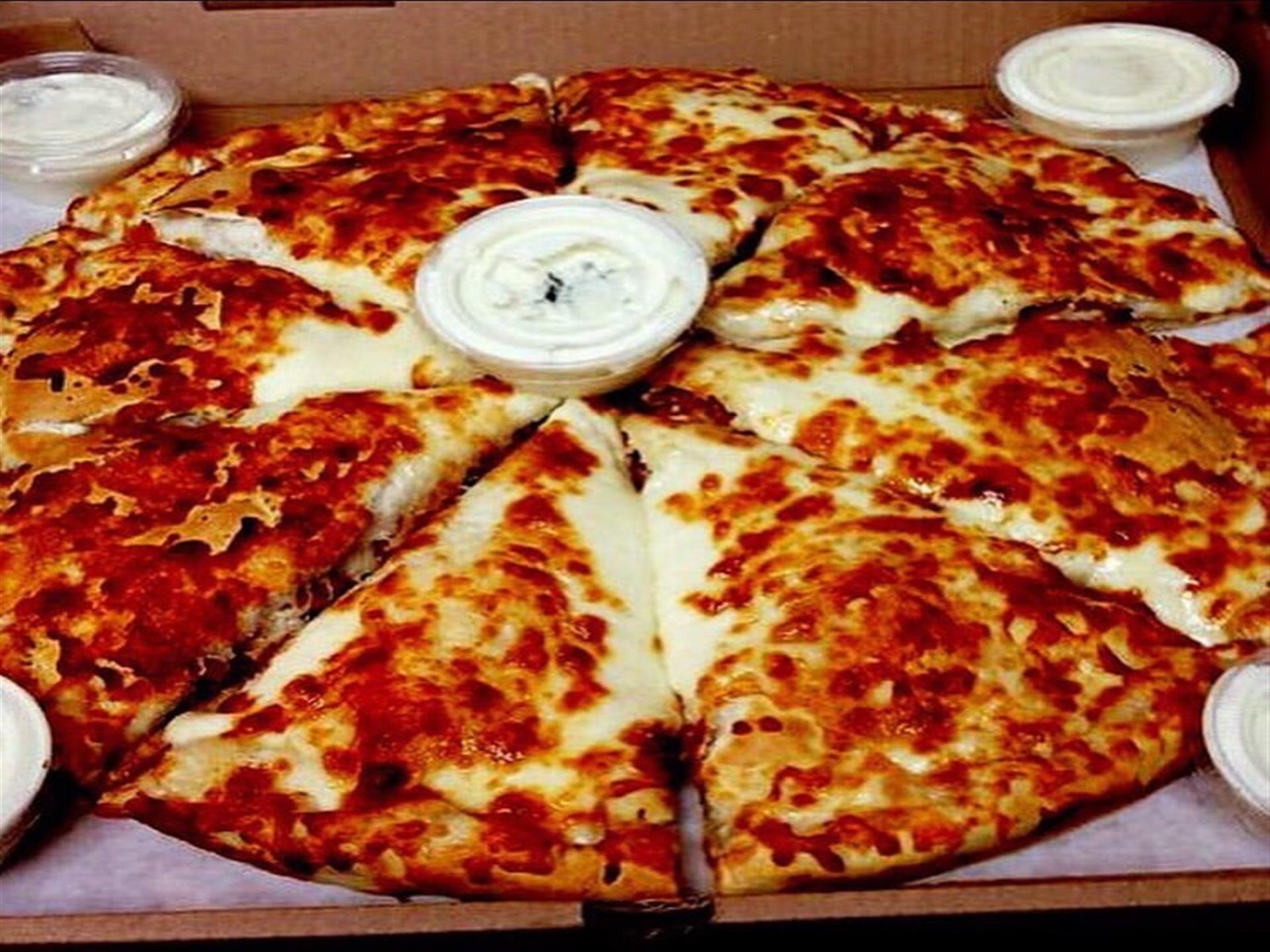 Pizza pie in pizza box with ranch dressing on the side