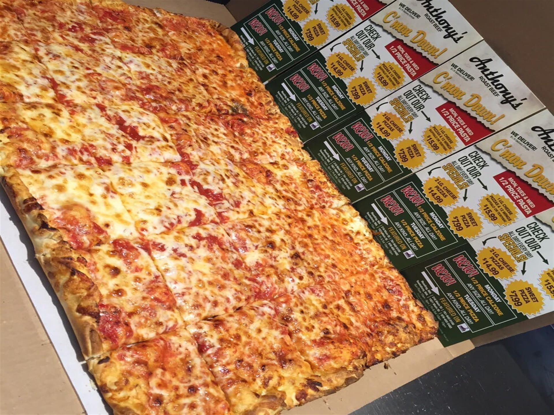 Party size pizza. 24 square slices.  Behind pizza are Anthony's coupons.