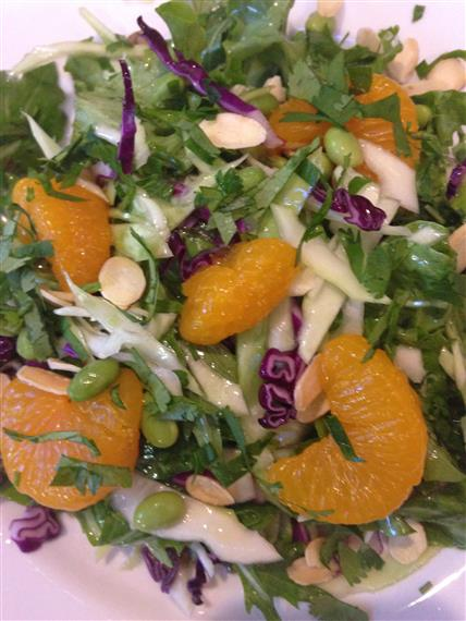 mixed greens with orange slices, nuts, and red cabbage