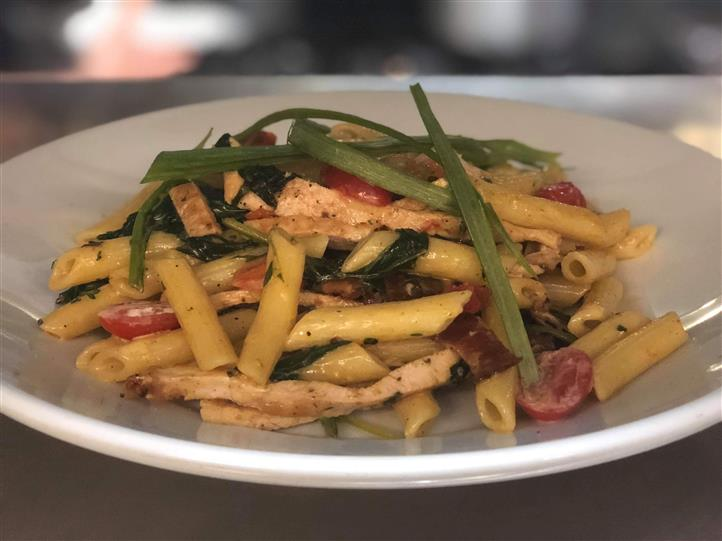 Penne with chicken, cherry tomatoes and greens
