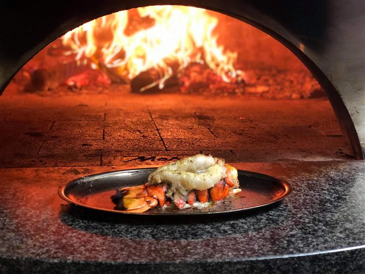 Wood-fired lobster in front of a wood-fired oven