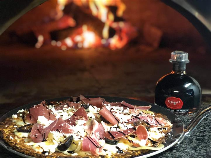 A pizza with sauce, black olives, prosciutto, garlic, topped with valsamic vinaigrette cream, next to a Modena vinaigrette bottle, in front of a wood-fired oven