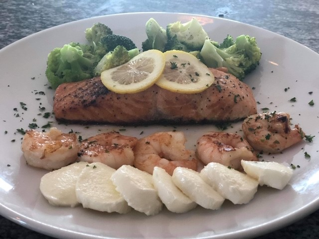 Grilled salmon topped with lemon slices served with shrimp, mozzarella and cauliflower