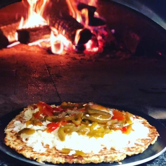 A wood-fired pizza with white sauce in front of the wood-fired oven