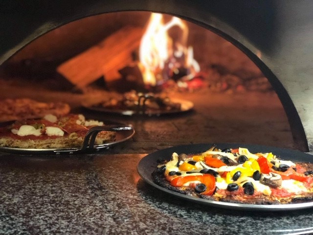 3 different wood-fired pizzas in front of the wood-fired oven