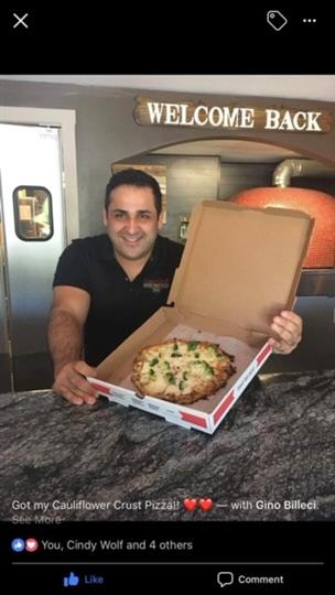 A Happy man holding a pizza in box posing for photo