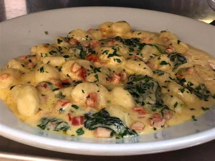 Gnocchi with spinach and tomatoes in a creamy alfredo sauce