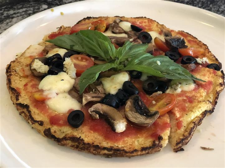 Wood-fired pizza with sauce, mozzarella, black olives, cherry tomatoes, mushrooms and basil