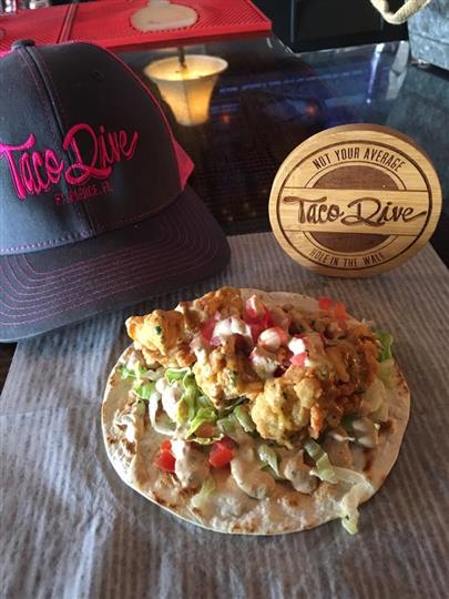 A taco with fried fish next to a blue Taco Dive hat