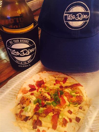A taco in front of a bottled beer and a blue Taco Dive hat