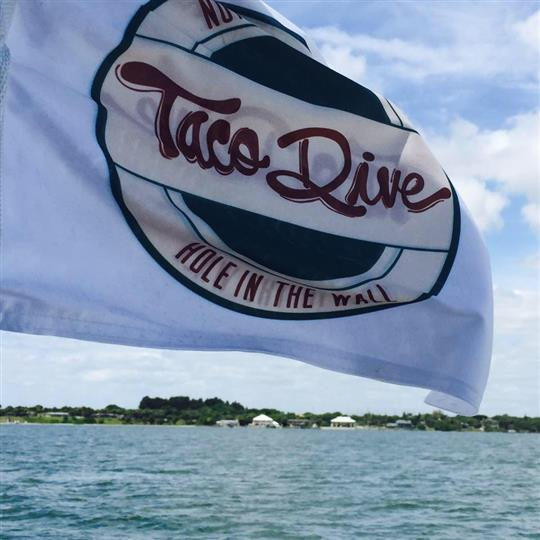 An outdoor shot of the taco dive flag in front of the sea