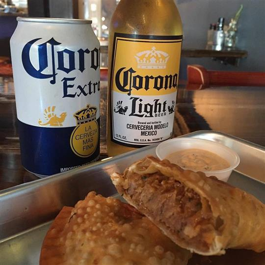 A tray with two pork tortas served with a dipping sauce, next to a can of corona extra and a bottle of corona light