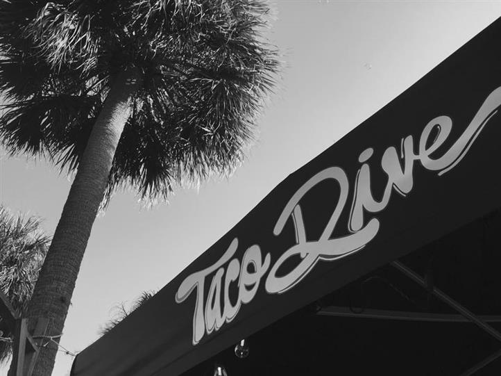 Black and white outdoor photo of an awning with the Taco Dive logo on it