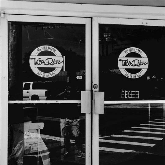 A photo of the glass central door of the restaurant having two taco dive logo filters