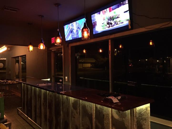 Interior shot of the empty restaurant's bar with two tv screens on