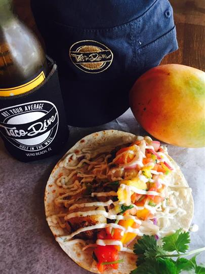A taco next to a mango, a blue hat and a bottle of beer