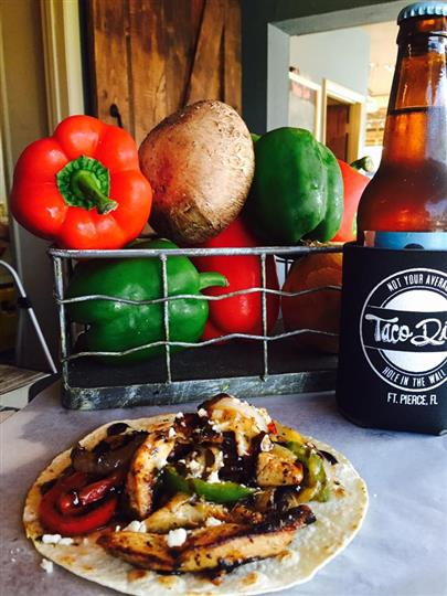 one taco with grilled chicken and vegetables on a table in front of a basket with red and green peppers and potatoes. Served with a beer bottle in a Taco Dive koozie.