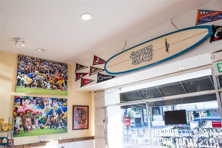 various decorative items hanging on the inside walls such as a surf board, photo frames and sports team flags