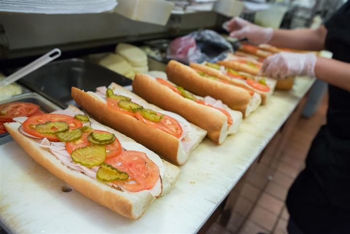 various sandwich orders being prepared in the kitchen
