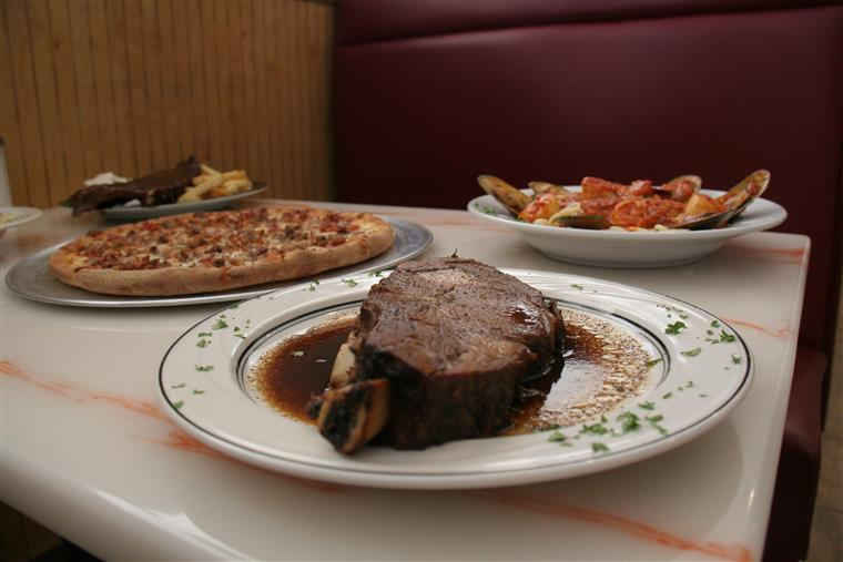 steak on a plate with a whole pizza and pasta dish in the background