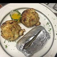 two crab cakes and a baked potato