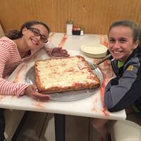 two young girls smiling at a table with a square cheese pizza