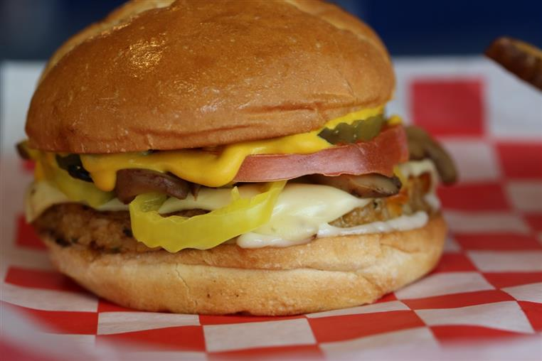 chicken sandwich topped with tomato, banana peppers and pickles