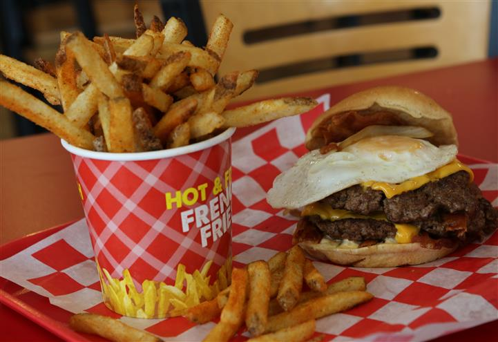 double bacon cheeseburger with a fried egg and a side of fries