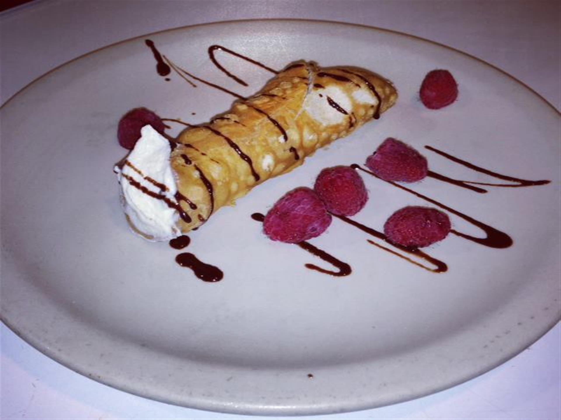 cannoli drizzled with chocolate and a few raspberries on a plate