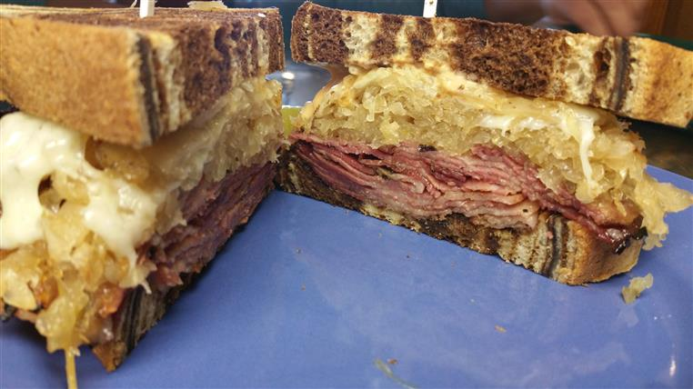 In-house smoked corned beef reuben cut in two