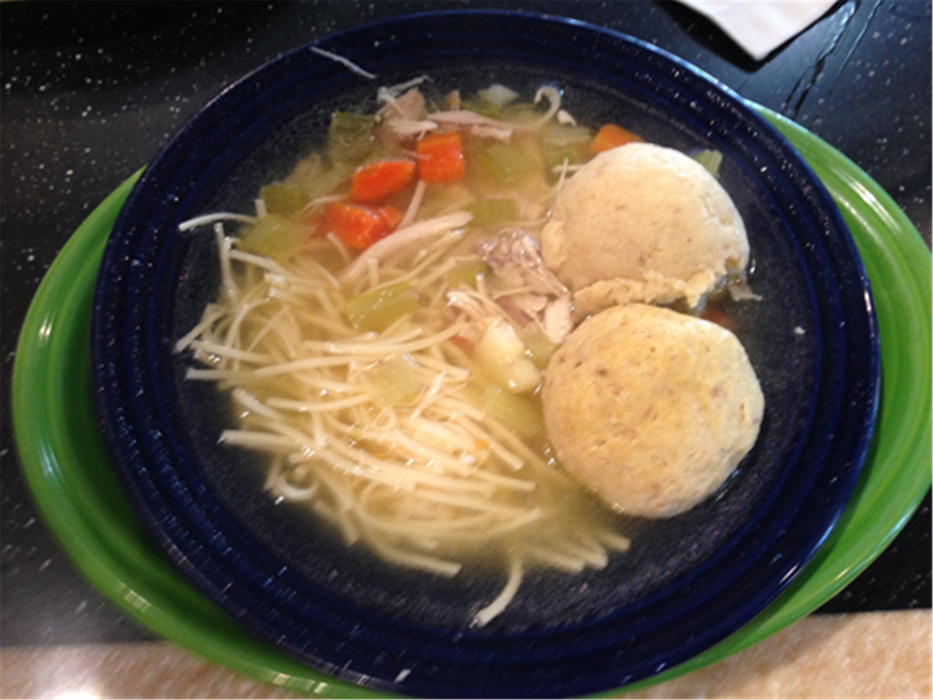 matzo ball soup with chicken, carrots, and celery