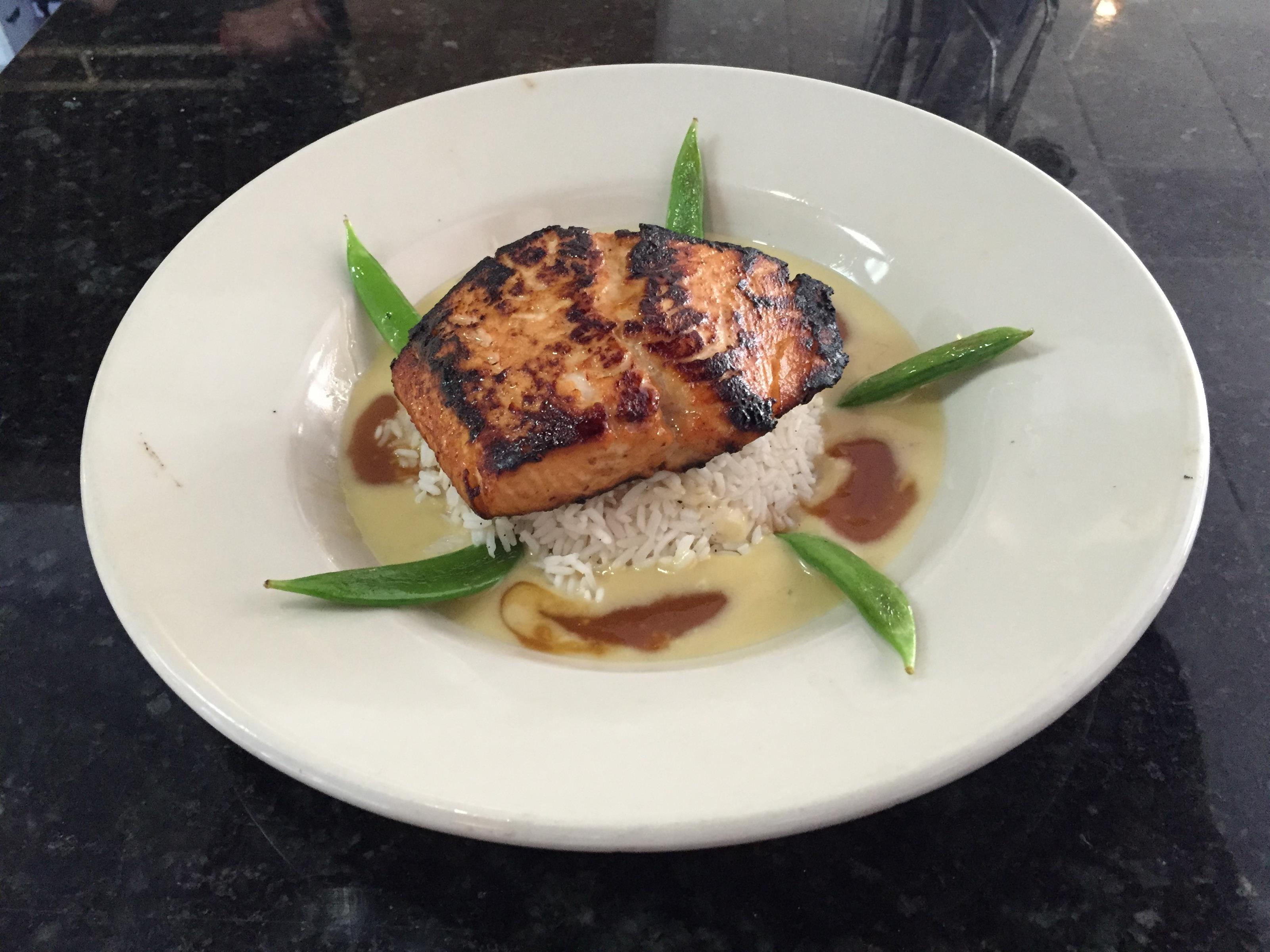 seared salmon on top of white rice with a creamy broth on the bottom