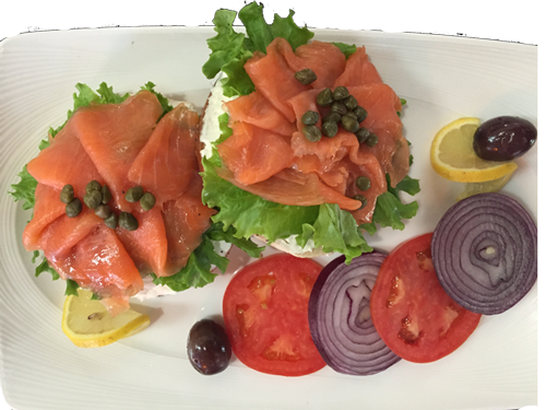 lox, cream cheese, and lettuce toast with an olive, tomato, and a red onion on the side